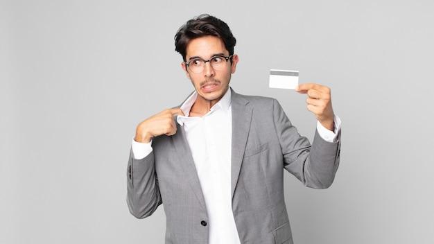 Jonge spaanse man voelt zich gestrest, angstig, moe en gefrustreerd en heeft een creditcard