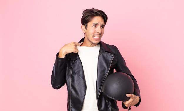 Jonge spaanse man voelt zich gestrest, angstig, moe en gefrustreerd. motorrijder concept