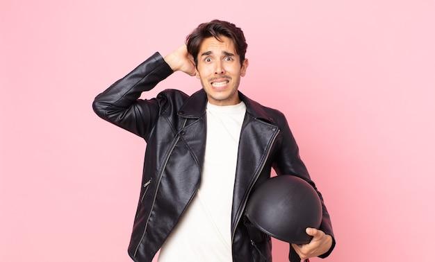 Jonge spaanse man voelt zich gestrest, angstig of bang, met de handen op het hoofd. motorrijder concept