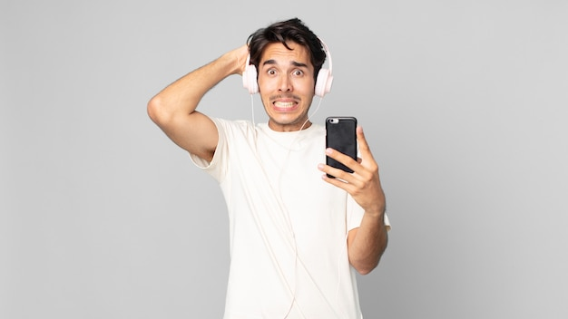 Jonge spaanse man voelt zich gestrest, angstig of bang, met handen op het hoofd met koptelefoon en smartphone