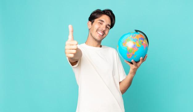 Jonge spaanse man voelt zich trots, glimlacht positief met duimen omhoog en houdt een wereldbolkaart vast