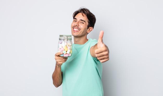 Jonge spaanse man voelt zich trots, positief glimlachend met duimen omhoog. gelei snoepjes concept