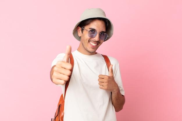 Jonge spaanse man voelt zich trots, positief glimlachend met duimen omhoog. zomer concept