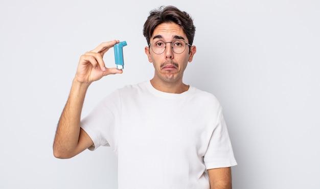 Jonge spaanse man voelt zich verdrietig en zeurt met een ongelukkige blik en huilt. astma concept