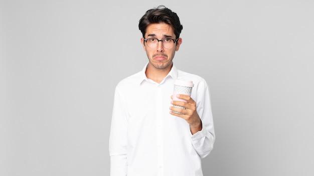 Jonge spaanse man voelt zich verdrietig en zeurt met een ongelukkige blik en huilt en houdt een afhaalkoffie vast