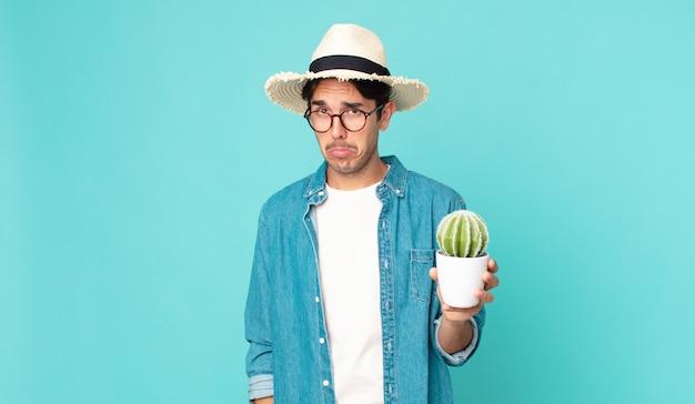 Jonge spaanse man voelt zich verdrietig en zeurt met een ongelukkige blik en huilt en houdt een cactus vast