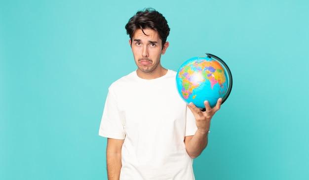 Jonge spaanse man voelt zich verdrietig en zeurt met een ongelukkige blik en huilt en houdt een wereldbolkaart vast