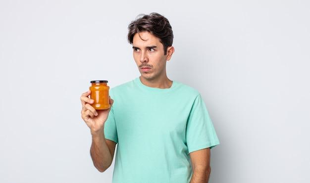 Jonge spaanse man voelt zich verdrietig, overstuur of boos en kijkt opzij. perzik gelei concept