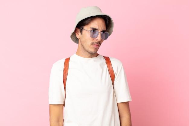 Jonge spaanse man voelt zich verdrietig, overstuur of boos en kijkt opzij. zomer concept