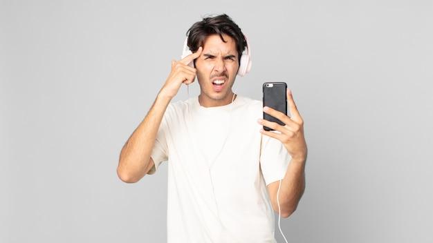Jonge spaanse man voelt zich verward en verbaasd en laat zien dat je gek bent met koptelefoon en smartphone