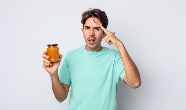 Jonge spaanse man voelt zich verward en verbaasd en laat zien dat je gek bent. perzik gelei concept