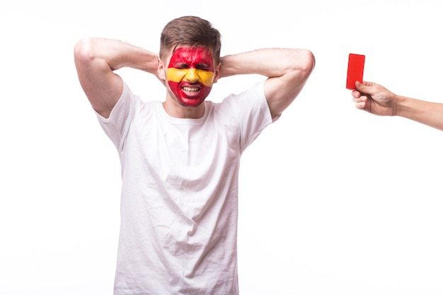 Jonge spaanse man voetbalfan met rode kaart geïsoleerd op een witte muur