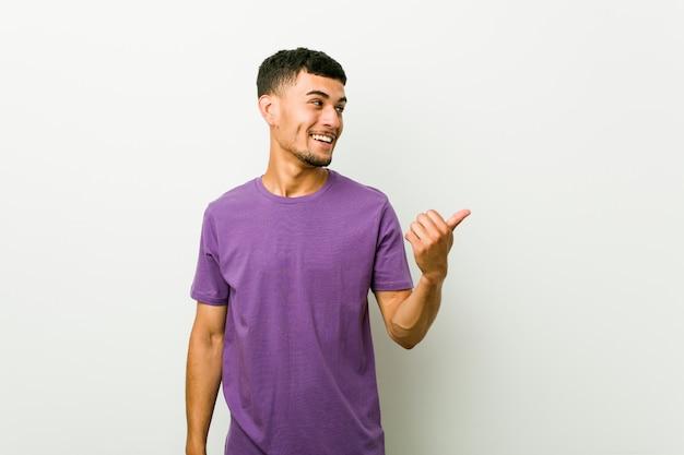 Jonge spaanse man wijst met duimvinger weg, lachend en zorgeloos.