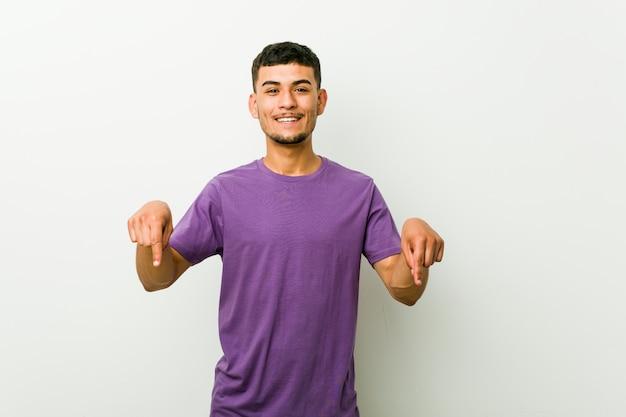 Jonge spaanse man wijst naar beneden met vingers, positief gevoel.