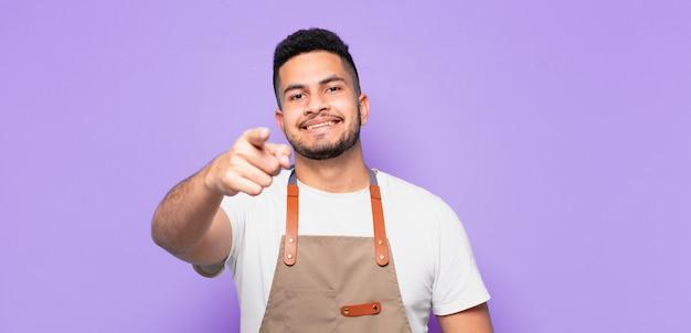 Jonge spaanse man wijst of toont. chef-kok concept