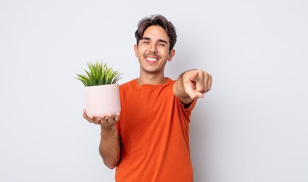 Jonge spaanse man wijzend op de camera die jou kiest. decoratief plantenconcept