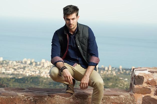 Jonge spaanse mannelijke model draagt een blauw shirt en een zwarte jas poseren in de buurt van een stenen muur