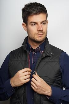 Jonge spaanse mannelijke model draagt een blauw shirt en een zwarte jas poseren tegen een witte muur