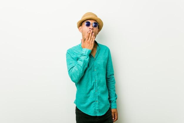 Jonge spaanse mens die de zomerkleren draagt ?? die een moe gebaar tonen die mond behandelen met hand.