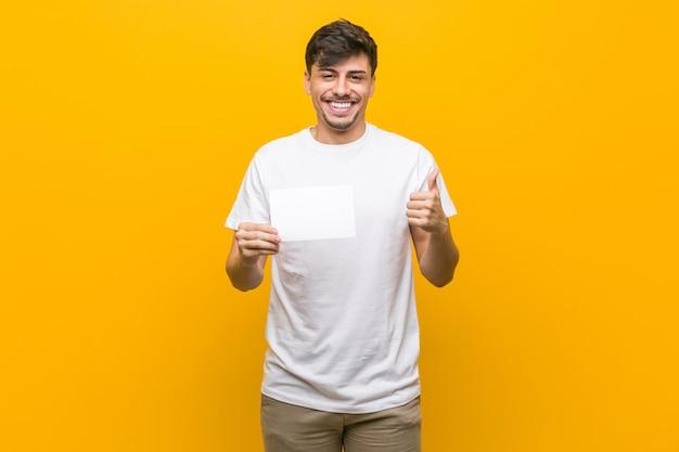 Jonge spaanse mens die een aanplakbiljet houdt glimlachend en duim opheffend