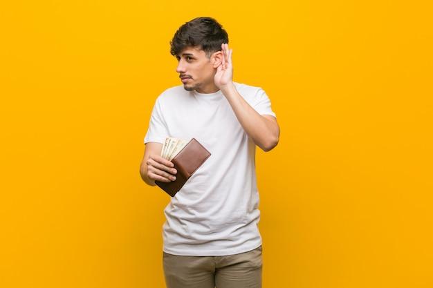 Jonge spaanse mens die een portefeuille houdt die aan een roddel probeert te luisteren.