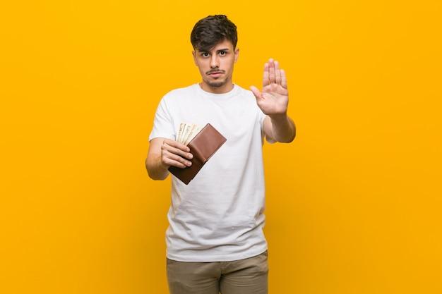 Jonge spaanse mens die een portefeuille houdt die zich met uitgestrekte hand bevindt die eindeteken toont, dat u verhindert