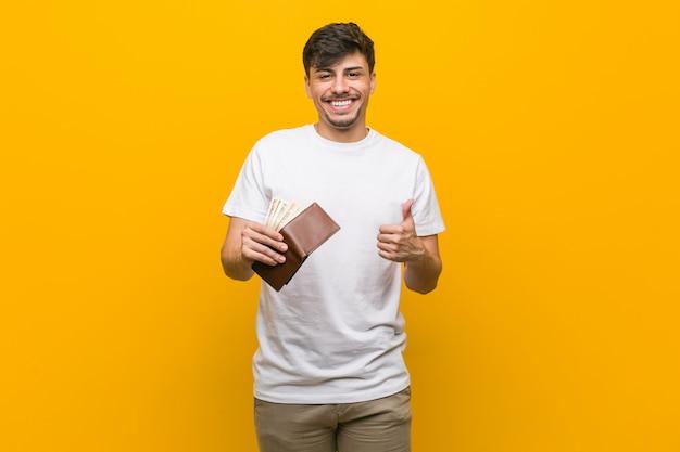 Jonge spaanse mens die een portefeuille houdt glimlachend en duim opheffend