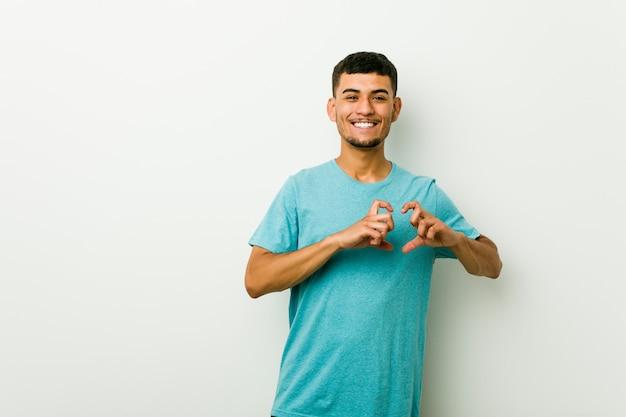 Jonge spaanse mens die en een hartvorm met handen glimlacht toont