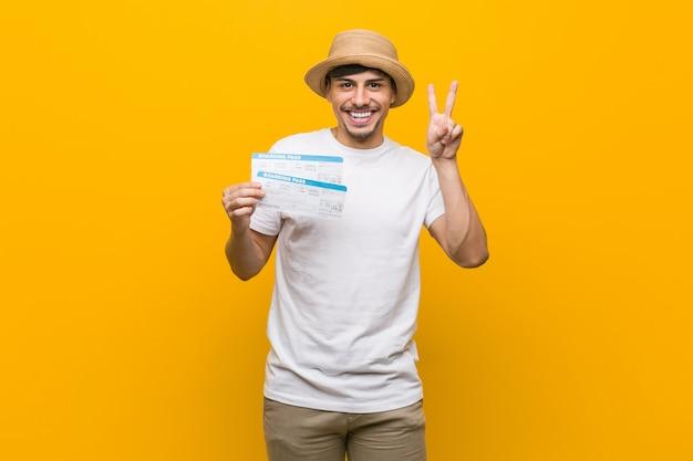 Jonge spaanse mens die luchtkaartjes houdt die overwinningsteken tonen en breed glimlachen.