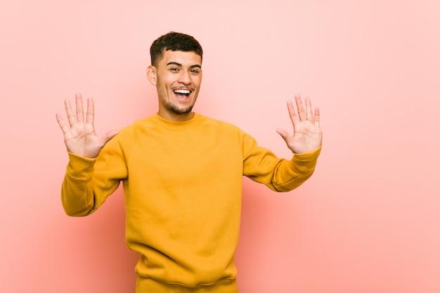 Jonge spaanse mens die nummer tien met handen toont.