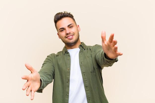 Jonge spaanse mens die vrolijk het geven van een warme, vriendschappelijke, houdende van welkome omhelzing glimlacht, die gelukkig en aanbiddelijk tegen geïsoleerde muur voelt
