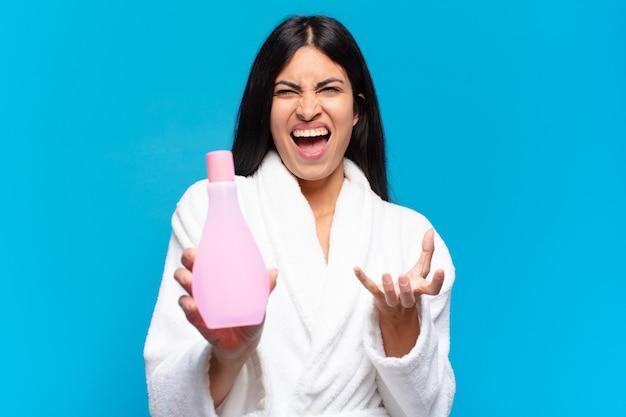 Jonge spaanse mooie vrouw met een gezichtsschoon product. cosmetisch concept