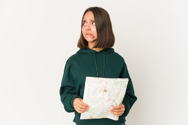 Jonge spaanse reizigersvrouw die een kaart in de war houdt, voelt zich twijfelachtig en onzeker.