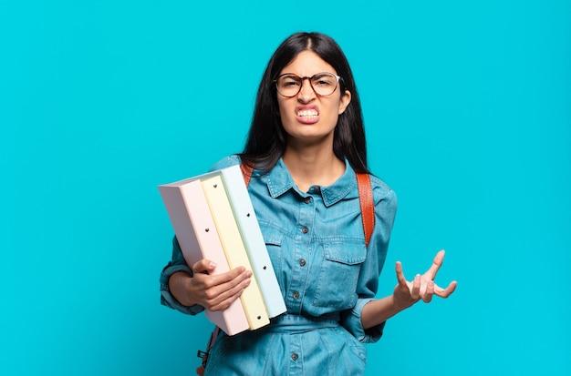 Jonge spaanse studentenvrouw die boos, geïrriteerd en gefrustreerd kijkt en wtf schreeuwt of wat er mis is met jou