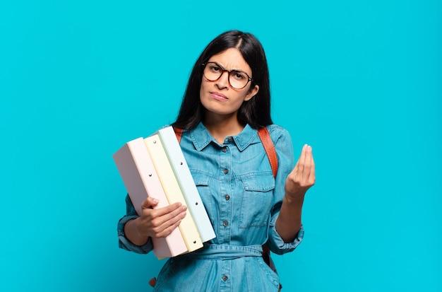 Jonge spaanse studentenvrouw die capice of geldgebaar maakt en u vertelt om uw schulden te betalen!