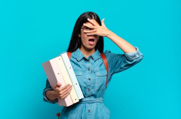 Jonge spaanse studentenvrouw die geschokt, bang of doodsbang kijkt, haar gezicht bedekt met de hand en tussen de vingers gluurt