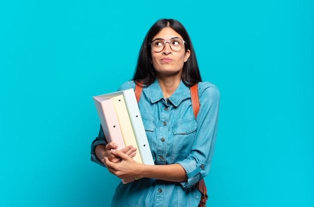 Jonge spaanse studentenvrouw die haar schouders ophaalt, zich verward en onzeker voelt, twijfelt met gekruiste armen en een verbaasde blik
