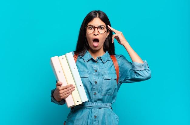 Jonge spaanse studentenvrouw die verrast, met open mond, geschokt kijkt en een nieuwe gedachte, idee of concept realiseert