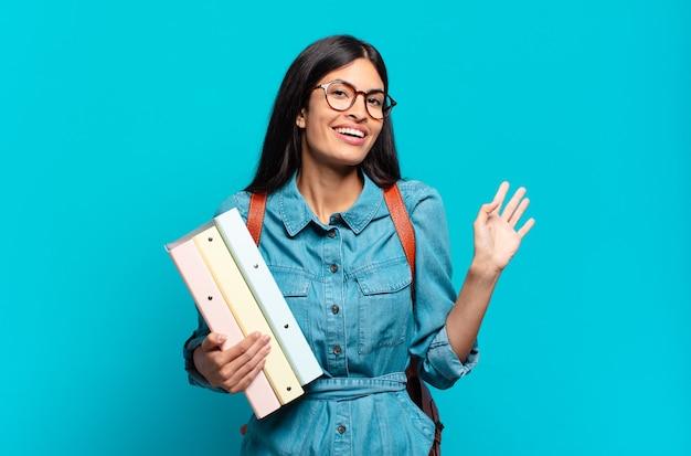 Jonge spaanse studentenvrouw die vrolijk en opgewekt lacht, met de hand zwaait, je verwelkomt en begroet, of afscheid neemt