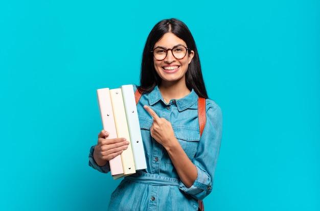 Jonge spaanse studentenvrouw die vrolijk glimlacht, zich gelukkig voelt en naar de zijkant en omhoog wijst, voorwerp in exemplaarruimte toont