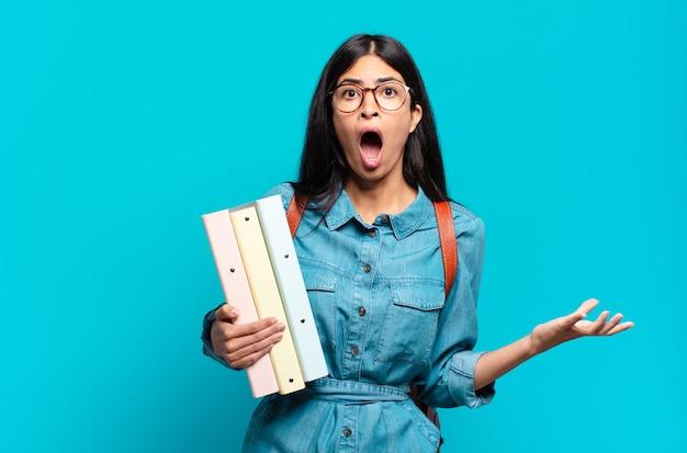 Jonge spaanse studentenvrouw die zich extreem geschokt en verrast, angstig en in paniek voelt, met een gestreste en geschokte blik