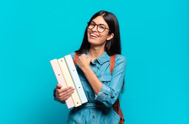 Jonge spaanse studentenvrouw die zich gelukkig, positief en succesvol voelt, gemotiveerd wanneer ze voor een uitdaging staat of goede resultaten viert
