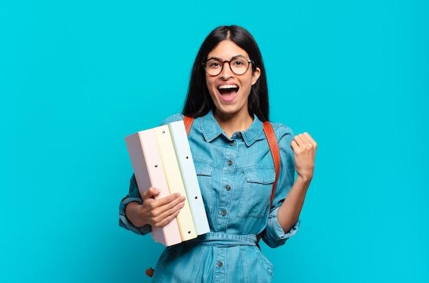 Jonge spaanse studentenvrouw die zich geschokt, opgewonden en gelukkig voelt, lacht en succes viert, en zegt wow!