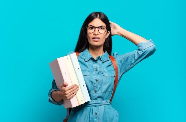 Jonge spaanse studentenvrouw die zich gestrest, bezorgd, angstig of bang voelt, met de handen op het hoofd, in paniek raakt bij een fout