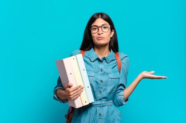 Jonge spaanse studentenvrouw die zich verward en verward voelt, twijfelt, weegt of verschillende opties kiest met grappige uitdrukking