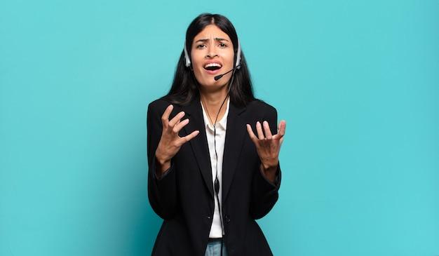 Jonge spaanse telemarketeer die er wanhopig en gefrustreerd, gestrest, ongelukkig en geïrriteerd uitziet, schreeuwt en schreeuwt