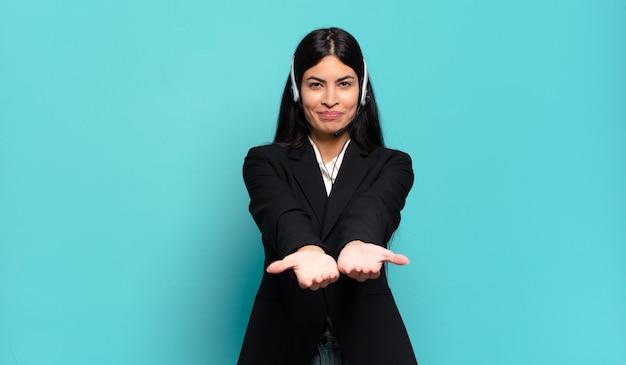 Jonge spaanse telemarketeervrouw die gelukkig met vriendelijke, zelfverzekerde, positieve blik glimlacht, een voorwerp of concept aanbiedt en toont
