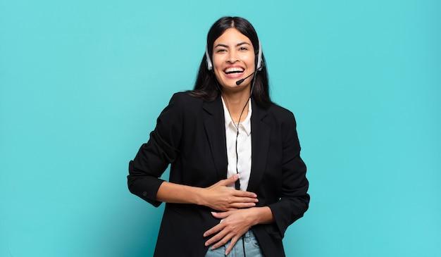 Jonge spaanse telemarketeervrouw die hardop lacht om een hilarische grap