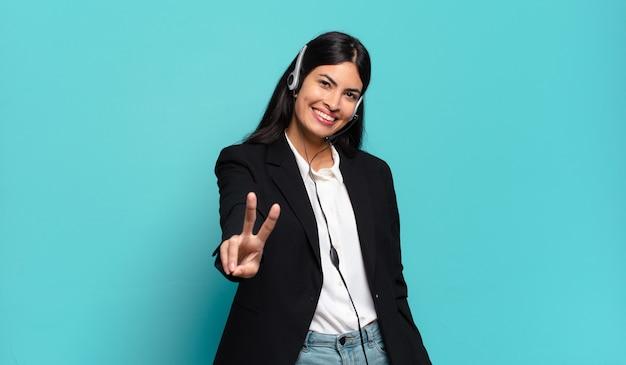 Jonge spaanse telemarketeervrouw die lacht en er gelukkig, zorgeloos en positief uitziet, gebarend overwinning of vrede met één hand