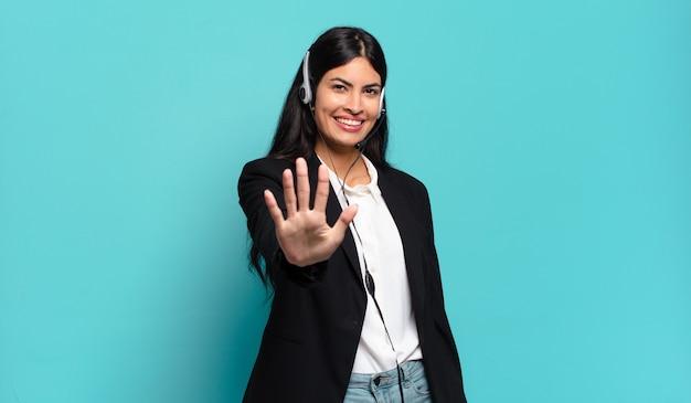 Jonge spaanse telemarketeervrouw die lacht en er vriendelijk uitziet, nummer vijf of vijfde toont met de hand naar voren, aftellend